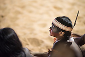 An indigenous boy watches the International Indigenous Games, in the city of Palmas, Tocantins State, Brazil wearing a traditional headband with feathers. Photo © Sue Cunningham, pictures@scphotographic.com 26th October 2015