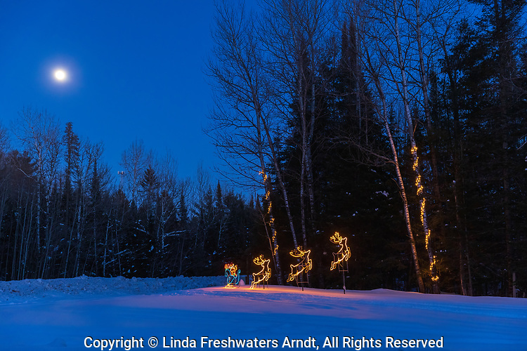 The blue light of twilight, a full moon, and holiday decorations in northern Wisconsin.