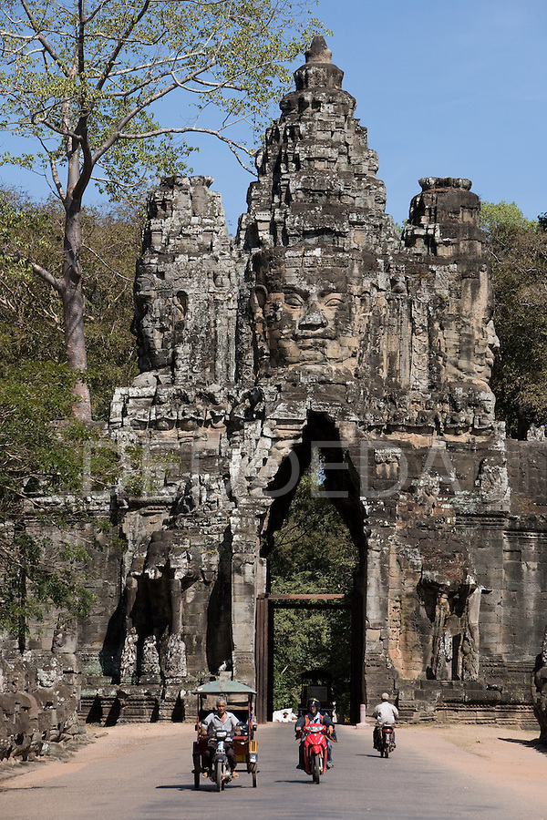 Locals drive tuk-tuks and motorcycles near a stone gate entrance in the ancient Khmer city of Angkor, a UNESCO World Heritage Site, in northwestern Cambodia, near Siem Reap.