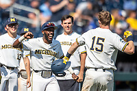 Michigan Wolverines outfielder Christian Bullock (5) greets teammate Jimmy Kerr (15) after his home run during Game 11 of the NCAA College World Series against the Texas Tech Red Raiders on June 21, 2019 at TD Ameritrade Park in Omaha, Nebraska. Michigan defeated Texas Tech 15-3 and is headed to the CWS Finals. (Andrew Woolley/Four Seam Images)