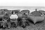Family keeping warm on  Brighton beach. Sussex England 1971. Deep Sea Anglers Club fishing boats.