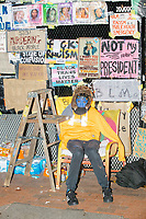 A person in blue facepaint, an apparent parody reference to the Blue Lives Matter pro-police movement, sits in front of anti-Trump and pro-Black Lives Matter signs covering a barricade surrounding Lafayette Square and the White House in preparation for anticipated street violence on the night of Election Day in Washington, D.C., on Tue., Nov. 3, 2020. Demonstrators in nearby Black Lives Matter Plaza remained peaceful.