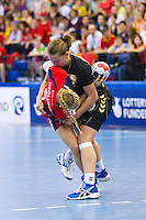 30 MAY 2012 - LONDON, GBR - Nina Heglund (GBR) of Great Britain (bottom, in red and blue) finds her path to goal blocked by Suzana Lazovic (MNE) of Montenegro (top, in black and gold) during the women's 2012 European Handball Championship qualification match at the National Sports Centre in Crystal Palace, Great Britain .(PHOTO (C) 2012 NIGEL FARROW)