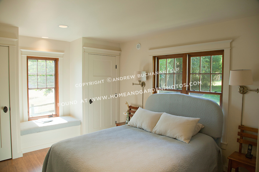 White paint, pale blue upholstery, and warm wood floors and window trim create a simple, inviting guest bedroom space.