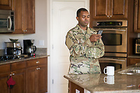 Off duty male US military soldier at home in his kitchen drinking coffee using the cell phone. For sale as stock photography, DOD compliant.