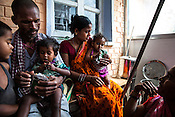 Caretakers and families feed RUTF to children at the government health centre in  Hanuman Nagar, Saptari, Nepal.
