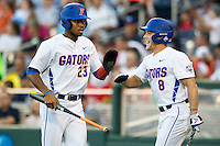 Florida Gators outfielder Buddy Reed (23) is greeted by teammate Harrison Bader (8) after scoring against the Miami Hurricanes in the NCAA College World Series on June 13, 2015 at TD Ameritrade Park in Omaha, Nebraska. Florida defeated Miami 15-3. (Andrew Woolley/Four Seam Images)