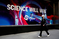 NEW YORK - NEW YORK - MARCH 23: A woman walks at Pfizer World Headquarters sidewalk on March 23, 2021 in New York. The Food and Drug Administration (FDA) says Pfizer's coronavirus vaccine can be stored in normal freezers for two weeks, instead of storage at ultra-cold temperatures. (Photo by John Smith/VIEWpress)