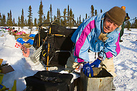 Dee Dee Jonrowe mixes food for her sled dogs @ camp in Cripple 1/2way point 2006 Iditarod Interior AK Winter
