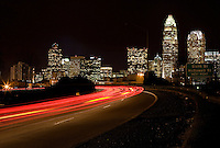 A blur of tail lights race by the Charlotte, NC, skyline.