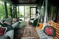 Screened porch with wicker furniture and brick floor makes indoor-outdoor room