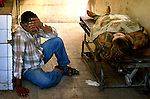 An Iraqi grieves over his dead sister after finding her at the morgue on June 23, 2004. She was among the two dead when an IED detonated in Baghdad.  (photo by Khampha Bouaphanh)