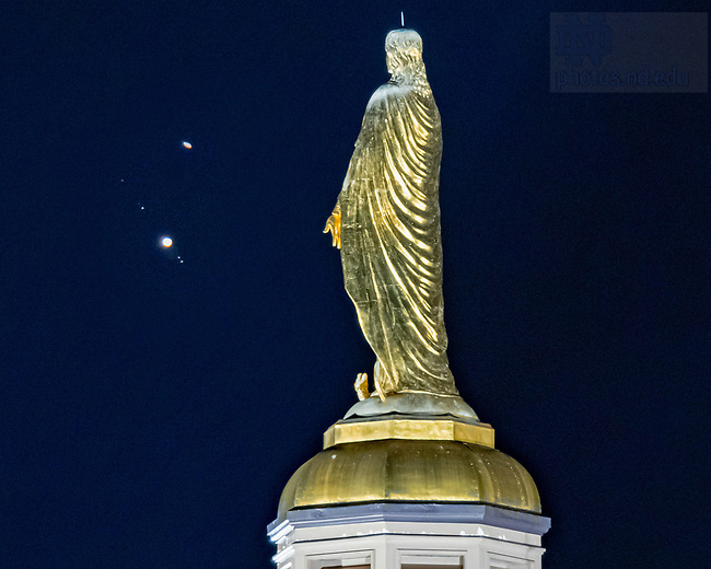 December 20, 2020; The planets Saturn (top) and Jupiter (with Galilean moons visible) seen behind the Mary statue on the Golden Dome. The orbits of the two planets overlap and visually appear to nearly merge in what is known as The Great Conjunction. NOTE: Photo is a composite of two images for purposes of having both the statue and planets in focus, which is not possible in a single exposure. (Photo composite by Matt Cashore/University of Notre Dame)