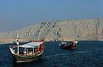 Peninsule du Musandam vers le detroit d'Ormuz. Des dhows ou batils - bateaux traditionnels a la roue ornee de coquillages - naviguent dans le fjord Sham profond de 17 km est domine par des falaises de plus de 1000 m de haut. Sultanat d'Oman. Moyen Orient.