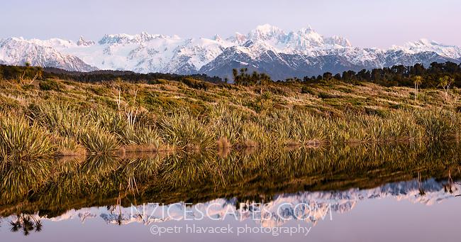 Alpen glow of twilight over Southern Alps with Mt. Tasman and Aoraki, Mt. Cook from Three Mile beach near Okarito, Westland Tai Poutini National Park, West Coast, UNESCO Wolrd Heritage Area, New Zealand, NZ
