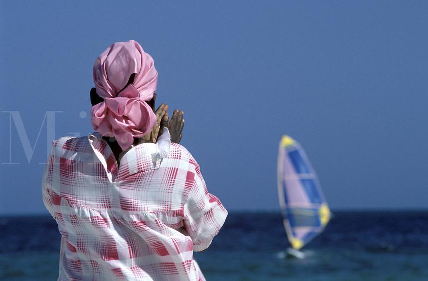Kenyan woman on beach looking at windsurfer out at sea
