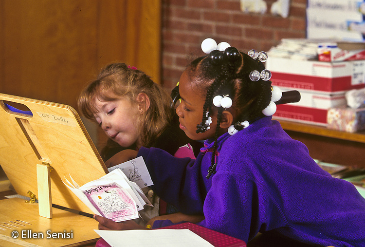 MR / Schenectady, New York. Zoller Public School, Inclusion Class, grade 1. Girl (6, African American) helps girl (6, cerebral palsy) at independent work time. Girl uses special adaptive desk so she can write easily. MR: Her4 All5 © Ellen B. Senisi