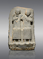 Hittite monumental relief sculpture of of two seated figure, not a typical Hittite style with a lot of other influences. Late Hittite Period - 900-700 BC. Adana Archaeology Museum, Turkey. Against a grey background
