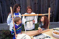Native American weaver demonstrates Raven's Tail Design for her family members.