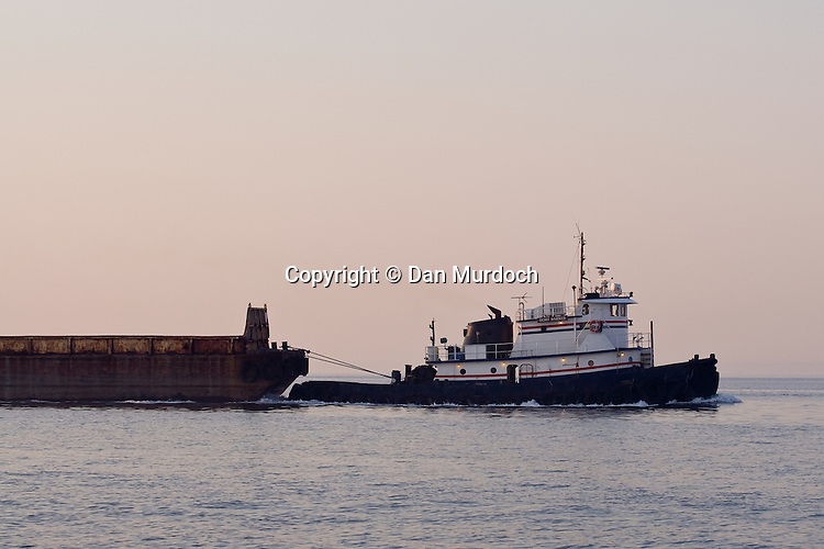 Tug Boat pulling barge in the early morning
