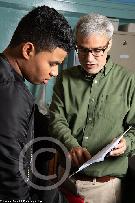 Education high school classroom scenes male science teacher talking to male student about his work