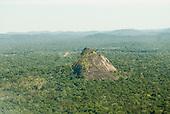 Pará State, Brazil. Aldeia Kendjam (Kayapo). Sacred rock rising from the forest floor.