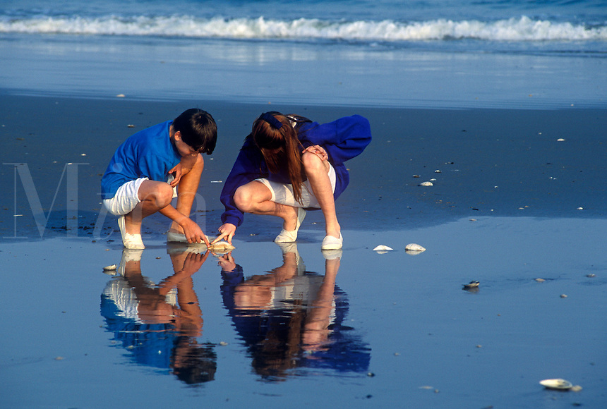 Siblings exploring on the beach.<br />