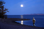 Full moon shines on lone man as he strolls along the shoreline.