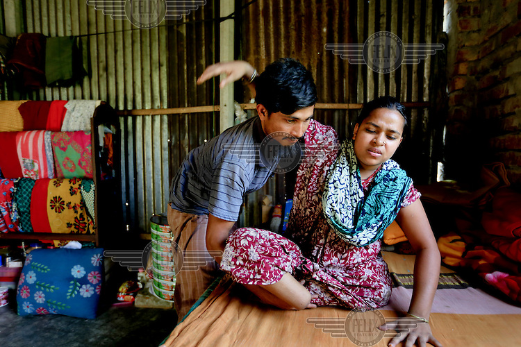 Rebeka Khatun helped by her husband. They were both sewing machinists at a garments factory at the Rana Plaza. After the building collapsed Rebekah was trapped beneath the rubble for 20 hours and had to have both legs amputated. She was hospitalized for 10 months and underwent eight operations.<br /> <br /> The eight storey Rana Plaza complex, which housed a number of shops and offices as well as five garment factories that employed more than 3,000 people, collapsed on 24 April 2013. When the search for bodies ended on 13 May 2013 the death toll had reached 1,129, a further 2,515 people were injured. The day before the collapse a structural engineer had warned the businesses inside to immediately evacuate the building. Many did, but the garment workers were told to return to work by the factory owners and the building's owner, Mohammed Sohel Rana, who is a member of the ruling Awami League's youth front. Afterwards some workers said they had been forced back to work with threats of violence and withholding of pay. A report produced by the Bangladeshi government stated that Sohel Rana illegally added several upper floors to the building which was not designed for the extra weight. Furthermore the huge generators installed on the upper floors, needed to power the factories, shook the entire structure and when they were started on the morning of the disaster it was their vibrations that triggered the collapse. 32 brands sourced clothes from the Rana Plaza but only half of those have contributed to a compensation fund and of those that have only Primark have made a significant payment.