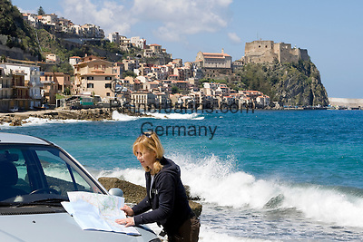 Italy, Calabria, Scilla: beach resort with castle Chianalea at entrance of Straits of Messina, woman with road map standing next to car