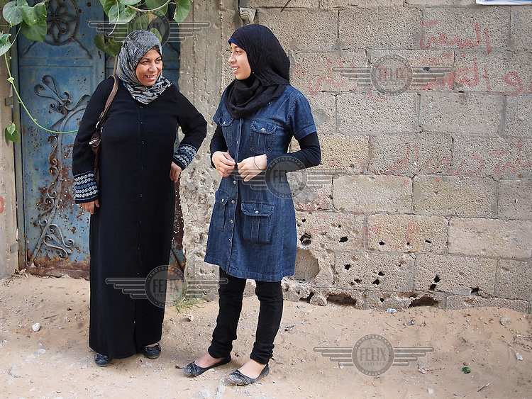 """Amira Al-Qerem (16) speaks with her step-mother on the place where her father was killed, in her old neighbourhood in Gaza City on October 27 2010. Amira was missing and presumed dead after she was injured by one of the same explosions that killed her father, brother and sister during the last days of the Israeli invasion of Gaza in 2009. She was found three days later, after her family thought they had buried her remains with those of the other three. She is one of the main subjects of the controversial documentary film """"Tears of Gaza"""" by director Vibeke Løkkeberg."""