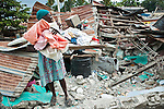 Une femme récupère des affaires dans les décombres de sa maison du quartier bas de Jacmel, le 18/01/2010. La ville, à 80km au sud de Port-au-Prince (Haiti), a été durement touchée par le séisme du 12/01/2010.