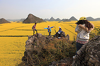 Luoping, Yunnan. On a hill surrounded by rape fields, young students come to have themselves photographed. Tourism is undergoing full expansion. 400 million Chinese travel in their country each year and 76 million travel overseas.