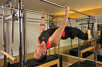 Pilates instructor on Cadillac apparatus