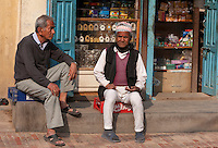 Nepal, Patan.  Two Men Sitting in front of a Store.