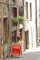 A street scene in Vienne, a restaurant called l'Estancot in the old town, with a sign and flowers in the window.  Vienne, Isère Isere, France, Europe
