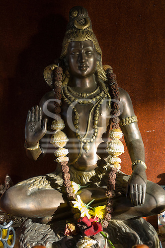 Golders Green, London. A bronze Hindu statue of Shiva with offerings.