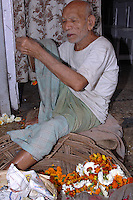 A man preparing flowers for sale in New Delhi, India