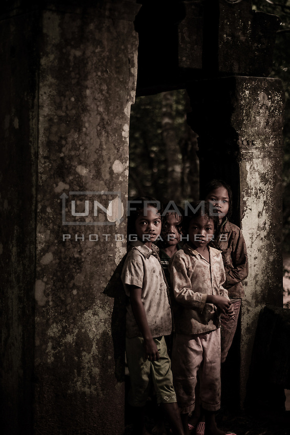 UNESCO World Heritage Site,  Ankgor wat temples . Children stand between the columns of a monumental temple. Local children  usually make their living by selling crafts and other products to tourists.   Seam Reap, Cambodia.