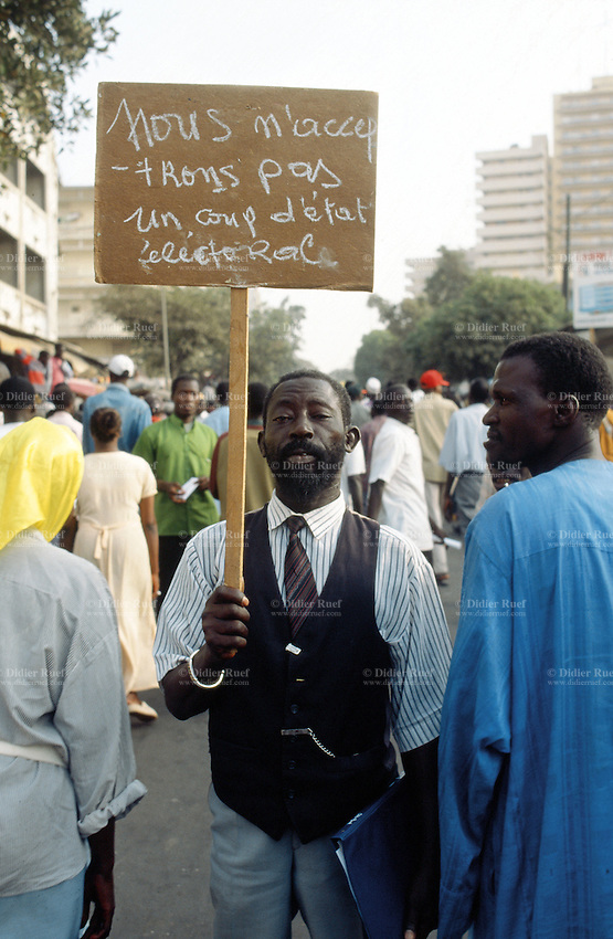 """Senegal. Dakar.Political meeting.Opposition leader Abdoulaye Wade from the FRTE party's supporter shows a written sign which says"""" We won't accept an electoral state coup""""  Abdoulaye Wade will later defeat his opponent  Abdou Diouf in the election results and will be  appointed as the new president of Senegal. © 2000 Didier Ruef"""