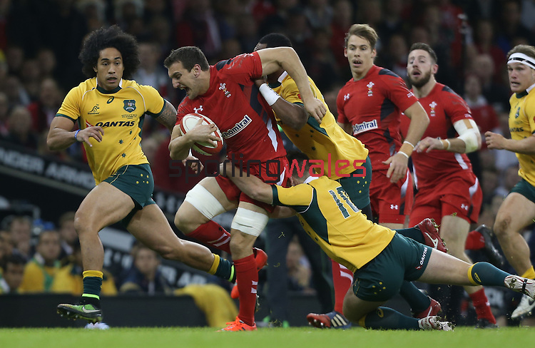 Captain Sam Warburton drives Wales forward despite the eftorts of Australian outside half Bernard Foley to stop him.<br /> Dove Men Series 2014<br /> Wales v Australia<br /> Millennium Stadium<br /> 08.11.14<br /> ©Steve Pope-SPORTINGWALES