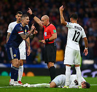 9th October 2021; Hampden Park, Glasgow, Scotland; FIFA World Cup football qualification, Scotland versus Israel;  Ofri Arad of Israel clutches his face as Lyndon Dykes of Scotland speaks to the referee