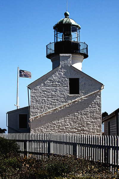 Lighthouse, flag, and fence at Point Loma
