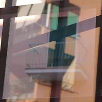 A glare on a window with grille, and a balcony with a closed shutter on the opposide side. An abstract photo (Rome, 2020).<br /> <br /> Un riflesso su una finestra con inferriata e un balcone con serranda abbassata sul lato opposto. Una foto astratta (Roma, 2020).