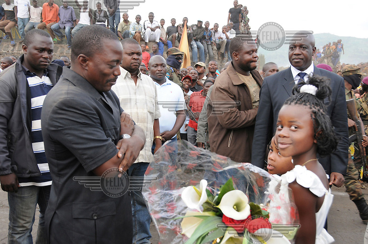 Presdent Joseph Kabila accepts flowers from two young girls on his visit to Goma.