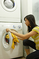Montreal (Qc) CANADA, July 24, 2007 - Model Released photo- A young asian woman use high efficiency (HE) detergent to wash clothes in a front loader washing machine.<br />