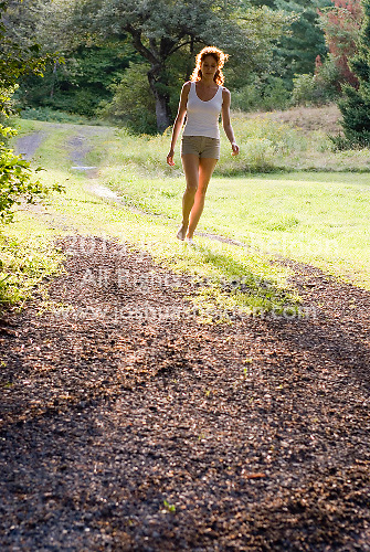 Red haired woman walking along grassy road