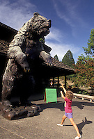 AJ3728, Portland, World Forestry Center, museum, grizzly bear, Oregon, Young six year old girl pretends to charge a large statue of a grizzly bear at the World Forestry Center in Washington Park in Portland in the state of Oregon.