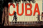 """Cuba, Havana, Cuban women walk beside a giant political """"CUBA"""" sign in Havana old town"""