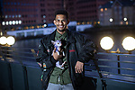 """© Joel Goodman - 07973 332324 - all rights reserved . 12/01/2020 . Salford , UK . KAYNE LEWIS (25) on the private shared terrace outside the block of his rented flat , which he shares with CHASE  (the 5 month old Chihuahua) and some fish , in apartment block """"Duet"""" , on Salford Quays in Greater Manchester . Photo credit : Joel Goodman"""